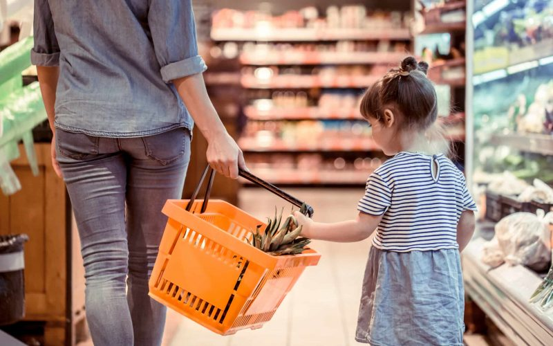 Girl placing object in grocery basket
